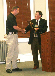 Commissioner Sage receives plaque from KSCPOST